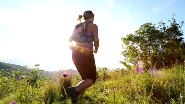 Young female runner pauses on hilltop field