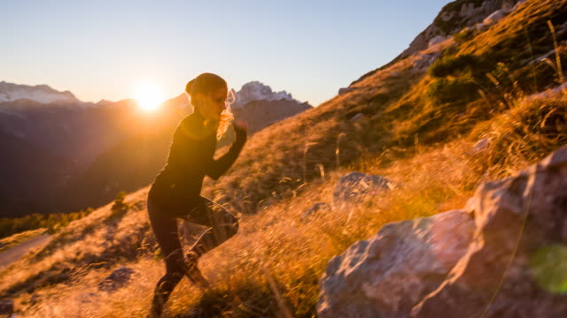 Young female runner running up the mountain at sunset