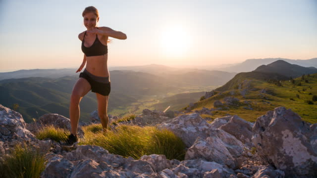 Young female runner running uphill a rocky landscape at sunset