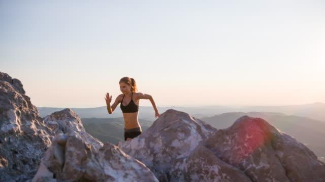 vídeos de stock, filmes e b-roll de jovem corredor feminino, corrida, corrida em ladeiras, uma paisagem rochosa - colina acima