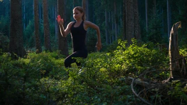 Junge weibliche Läufer Sporttraining im Wald bei Sonnenuntergang