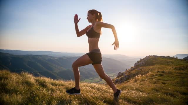 Jonge vrouwelijke atleet opleiding in de bergen