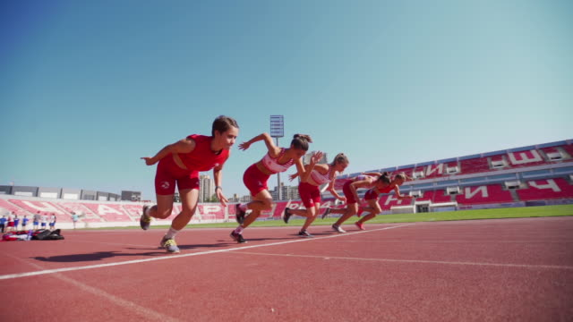 young female runners in starting blocks - pista di atletica leggera video stock e b–roll
