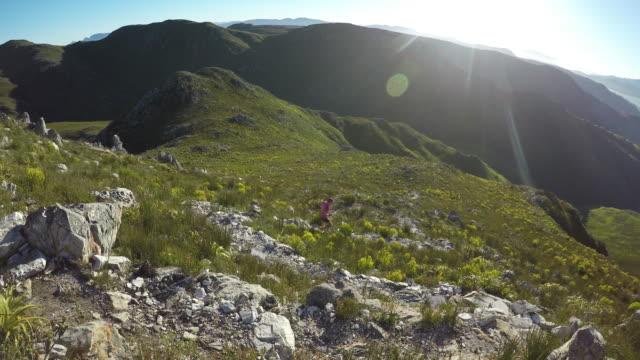vídeos y material grabado en eventos de stock de joven mujer corre por un camino de montaña hermosa - corredora de footing