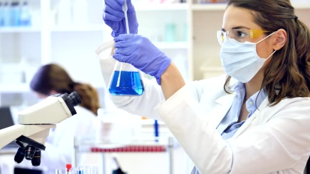 young female scientist conducts research in laboratory - female doctor stock videos & royalty-free footage