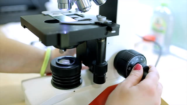 young female scientist looking on  microscope. - pathologist stock videos & royalty-free footage