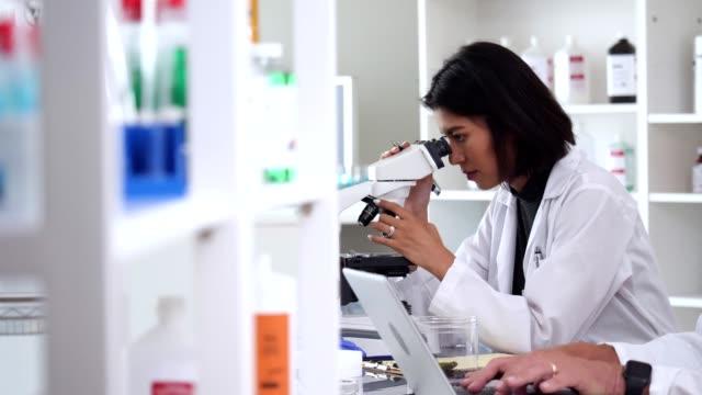 若い女性科学者が研究室で顕微鏡を使用 - バイオテクノロジー点の映像素材/bロール