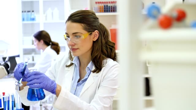 young female scientist works in research laboratory - becher video stock e b–roll