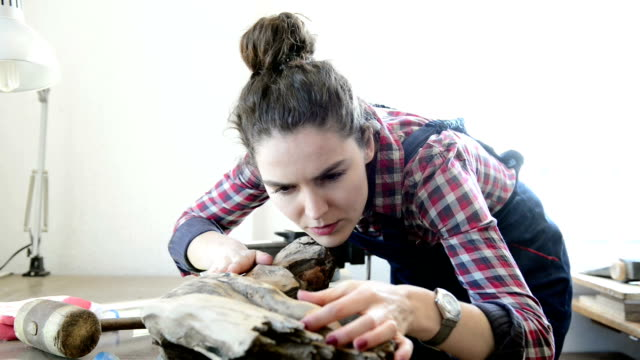Young female sculptor working with a log