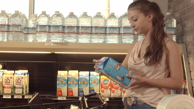 ms young female shopper picks milk carton from store shelf in grocery store - choice stock videos & royalty-free footage