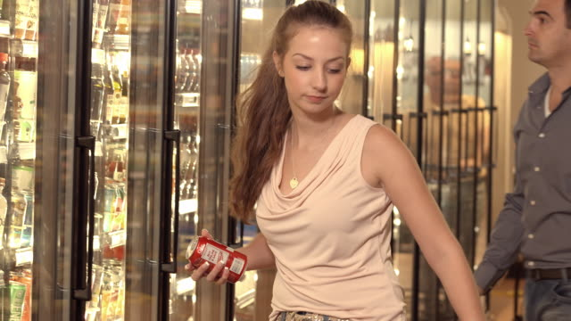 MS young female shopper pulls can of soda pop from refrigerated beverage section of supermarket