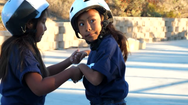 ms young female skateboarder holding hands with friend during summer skate camp - standing stock videos & royalty-free footage