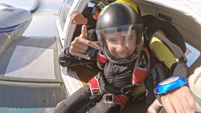 POV jonge vrouwelijke skydiver springen uit het vliegtuig wachten