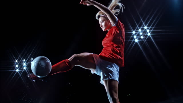 slo mo ld young female soccer player kicking the ball in the air on black background - サッカー選手点の映像素材/bロール