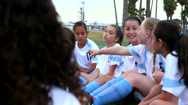 ms young female soccer players in discussion while sitting together on field - football team stock videos & royalty-free footage