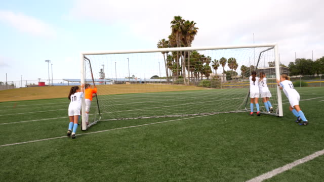 MS Young female soccer players moving goal into place before practice