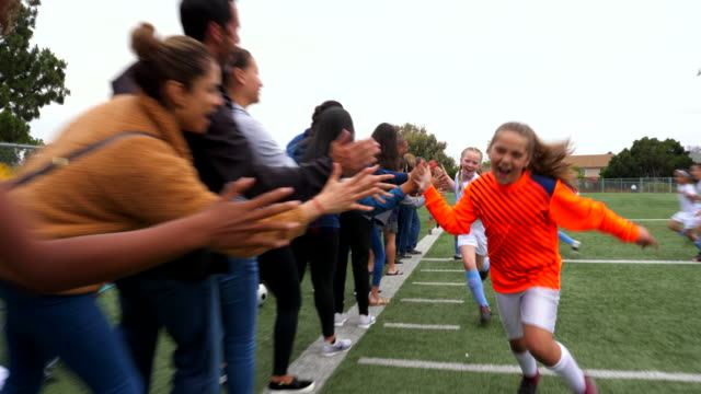 vidéos et rushes de ms young female soccer players running though line of high fives with families on sidelines after game - activité