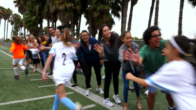 ms young female soccer players running though line of high fives with families on sidelines after game - parent stock videos & royalty-free footage