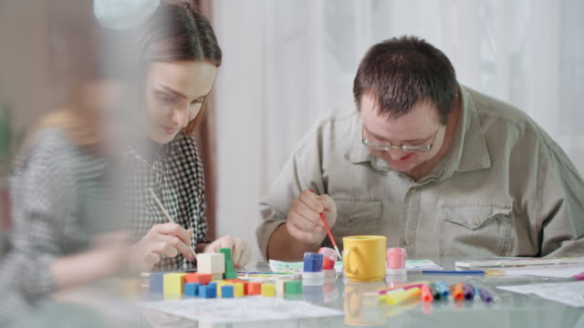 young female social worker and man with development disability painting picture together - doing a favour stock videos & royalty-free footage