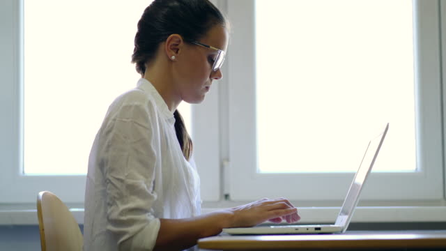 young female student using laptop - profile view stock videos & royalty-free footage