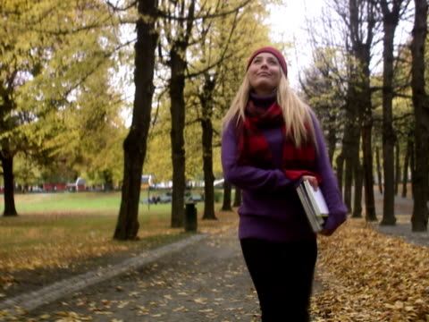 A young female student walking in a park Stockholm Sweden.