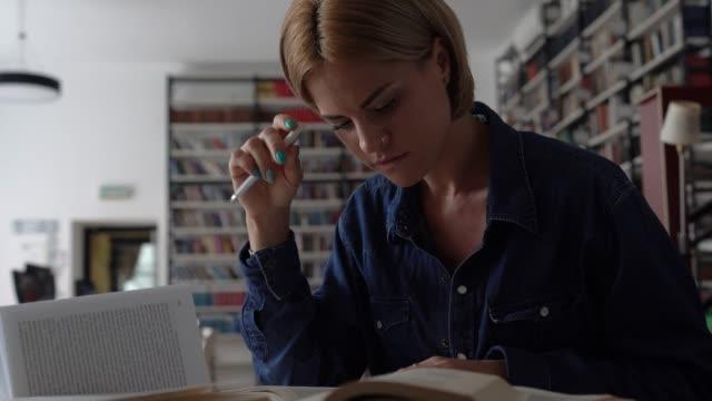 Junge Studentin mit kurzen Haarlesbüchern in der Bibliothek