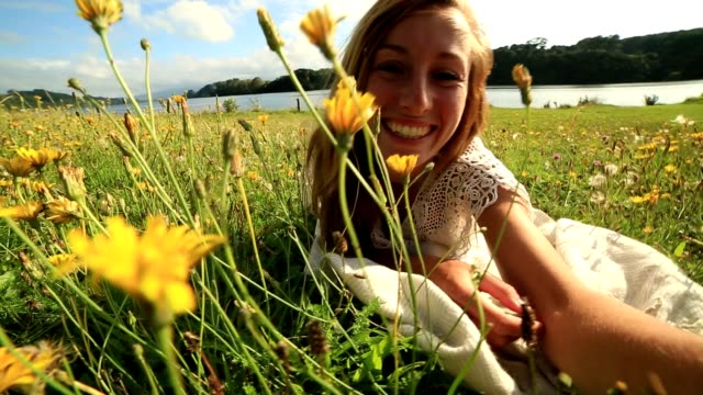 Young female takes a selfie in a wildflower meadow