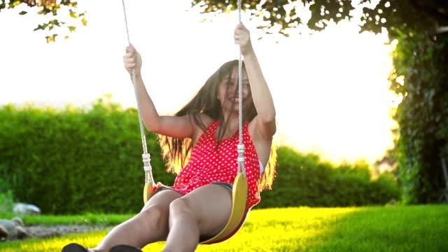 junge weibliche teen auf einem baum schwingen bei sonnenuntergang - shorts stock-videos und b-roll-filmmaterial
