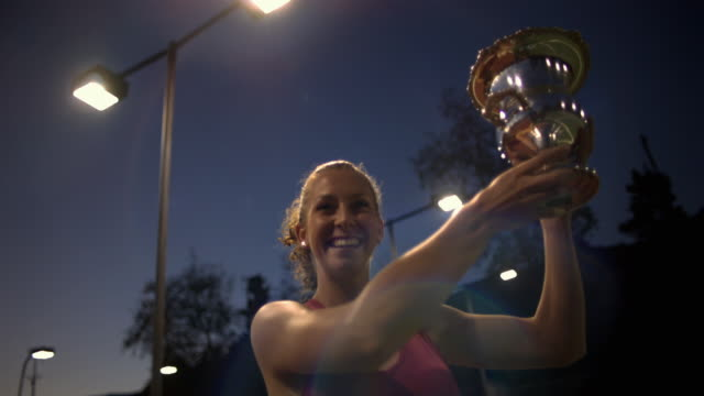 vídeos y material grabado en eventos de stock de cu, la, young female tennis player holding trophy, dusk, santa barbara, california, usa - ganar