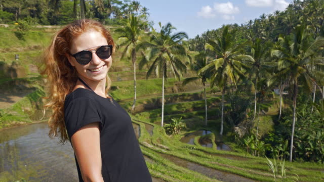 Young female tourist admiring Tegalalang Rice Terrace in Bali