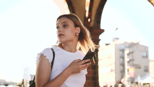 young female tourist holding smart phone while looking away in city - ハンドバッグ点の映像素材/bロール