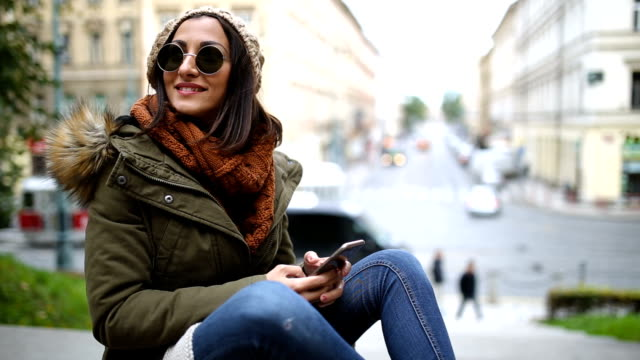 Young female tourist in Prague using phone
