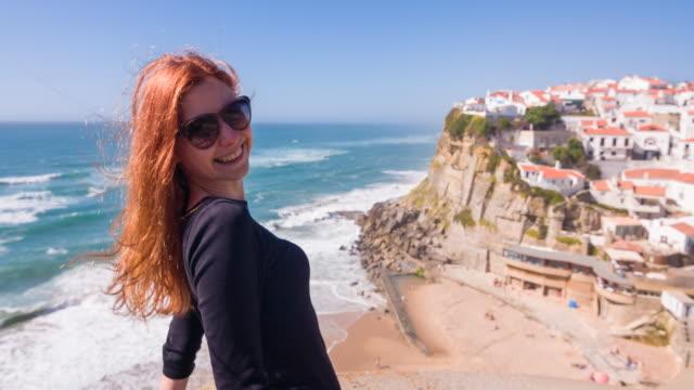 Jovem mulher em uma aldeia em penhascos com vista para o Oceano