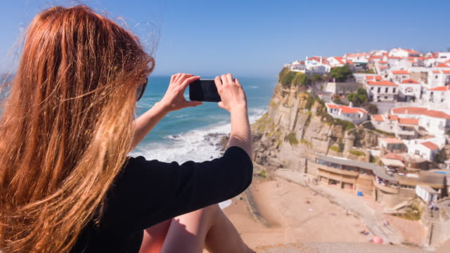 young female tourist photographing a village on cliffs by ocean - moving activity stock videos & royalty-free footage