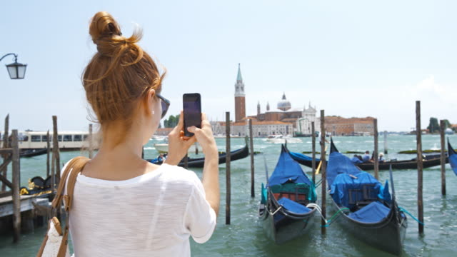Young female tourist taking photos of Venice, Italy