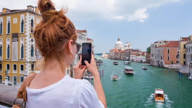 Junge Frau nimmt Fotos von Venedig, Italien