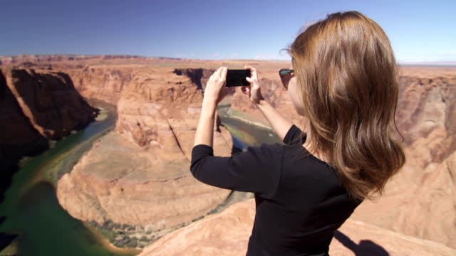 young female tourist taking pictures of grand canyon with smartphone - grand canyon bildbanksvideor och videomaterial från bakom kulisserna