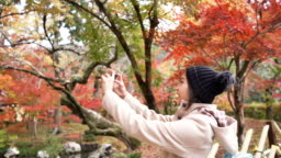 Young female tourist taking pictures on vacation autumn season at Japan