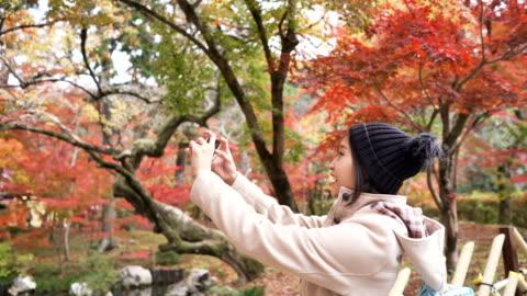 stockvideo's en b-roll-footage met jonge vrouwelijke toerist foto's nemen op vakantie herfstseizoen in japan - autumn