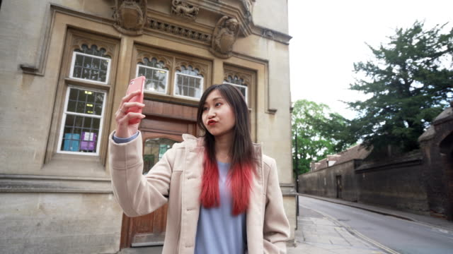 young female tourist taking selfie pictures on vacation - long distance relationship stock videos & royalty-free footage