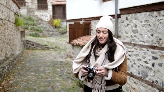 Junge weibliche Touristen Wandern und sightseeing auf den einsamen Straßen eines kleinen Dorfes.