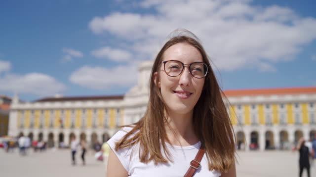 vídeos de stock, filmes e b-roll de turista fêmea nova que anda no quadrado de praca do comercio - tourist
