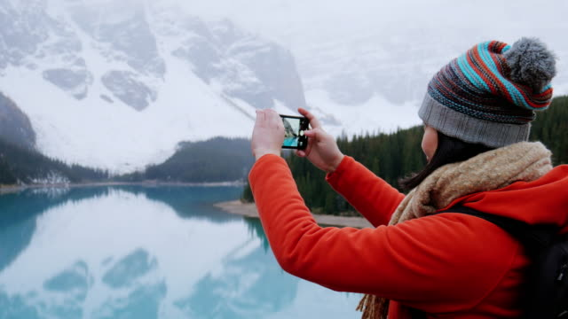young female traveler take a photo with her smartphone at moraine lake , alberta , canada - alberta stock videos & royalty-free footage