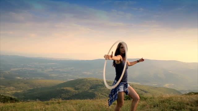 jonge vrouw met behulp van een hula hop op de berg