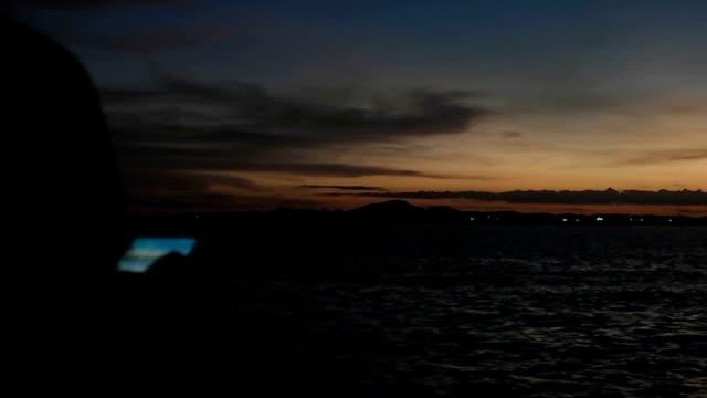 Young Female mittels Handy am tropischen Strand von Sunset.Girl mit einem Smartphone am Strand in der Nacht.