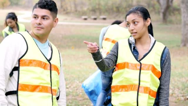Young female volunteer coordinator instructs volunteer during neighborhood cleanup