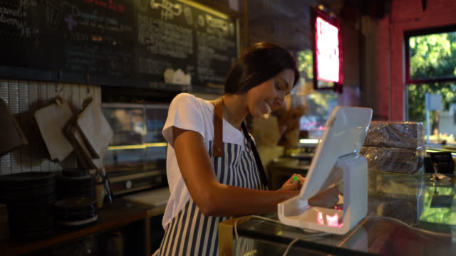vídeos de stock, filmes e b-roll de garçonete feminina jovem escrevendo algo no papel e em seguida, registrando no sistema em uma lanchonete - título de eleitor