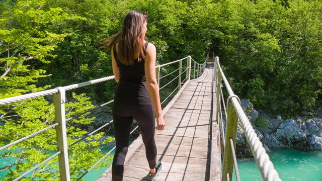 young female walking over a wooden suspension bridge - suspension bridge stock videos & royalty-free footage