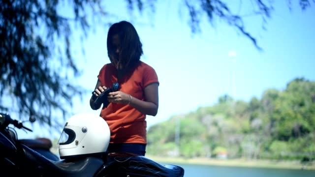 黒い革の手袋を着て、彼女のチョッパーに乗るためのヘルメットを置く若い女性, 湖の横に. - glove点の映像素材/bロール