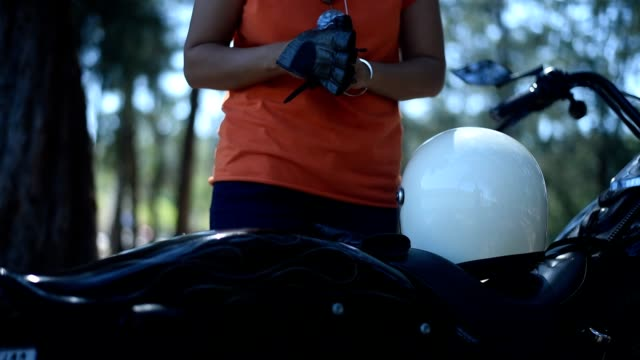 Young female wearing black leather gloves and putting on helmet for riding her chopper, beside the lake.